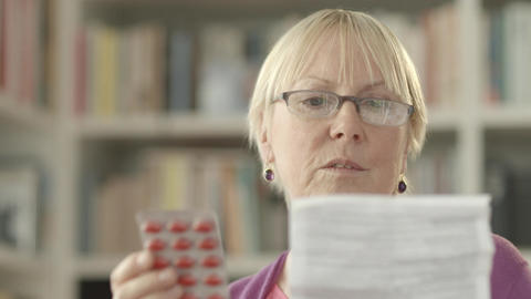 Senior woman with pills and prescription Stock Video Footage