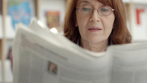 Elderly woman reading newspaper in library Stock Video Footage