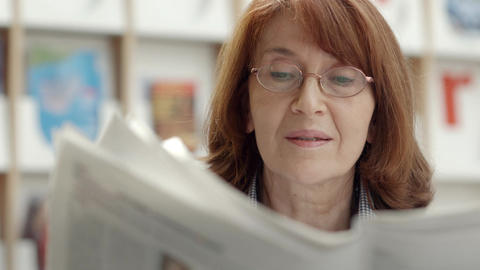 Elderly woman reading newspaper in library Footage