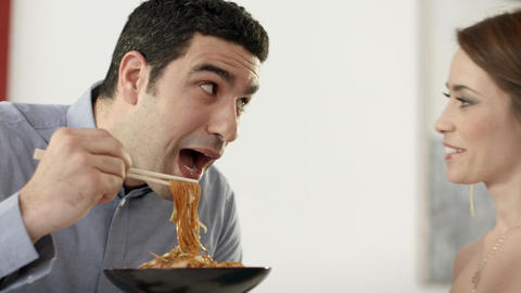 Couple having fun with spaghetti and chinese sticks Stock Video Footage