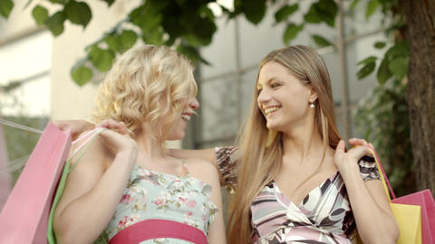 Two female friends smiling with shopping bags Stock Video Footage