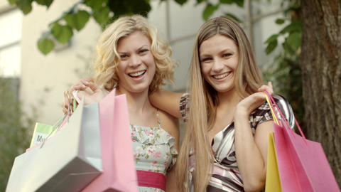 Two female friends smiling with shopping bags Footage