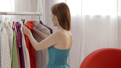 Woman trying out red dress in clothes shop Stock Video Footage