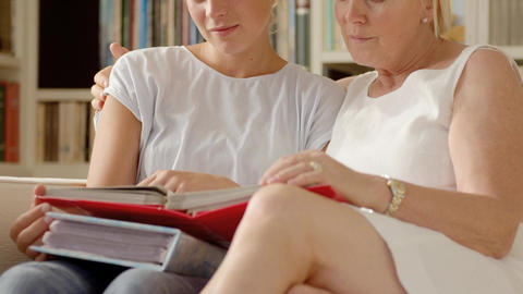 Mother and daughter looking at pictures in photo album Stock Video Footage