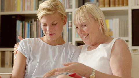 Mother And Daughter Looking At Pictures In Photo A stock footage