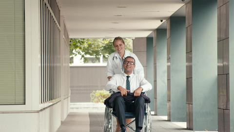 Female doctor assisting businessman on wheelchair Stock Video Footage