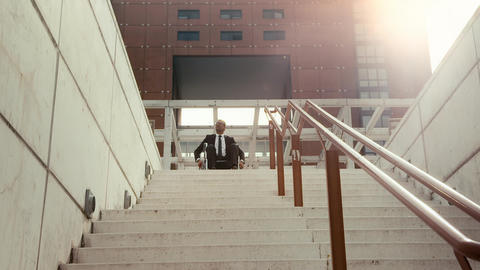 Businessman on wheelchair moving back from a stair Footage