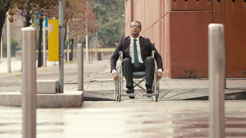 Businessman on wheelchair crossing a city street Stock Video Footage