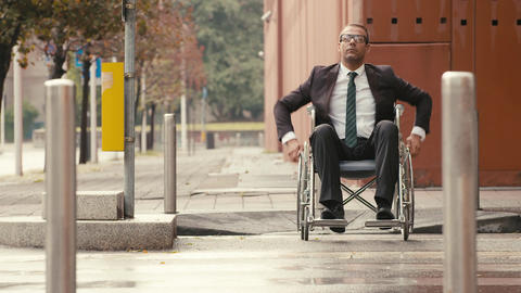 Businessman on wheelchair crossing a city street Live Action