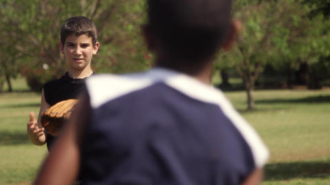 Two young boys playing baseball in park Footage