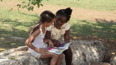 Two little girls reading book in city park Stock Video Footage