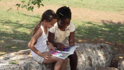Two little girls reading book in city park Footage