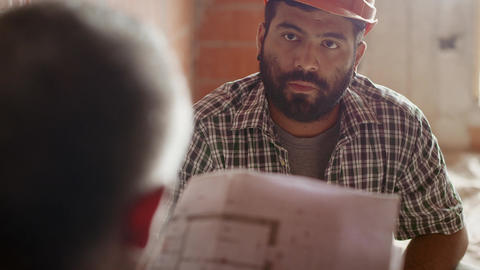 Two men discussing plan at work in construction site Stock Video Footage
