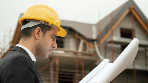 Architect in Construction Site Looking at Blueprint Footage