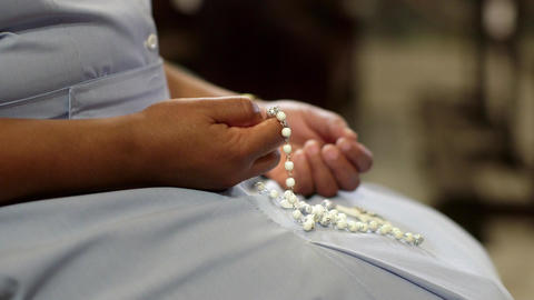 Catholic Sister Praying in Church and Holding Cross Stock Video Footage