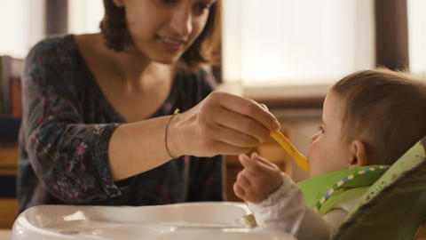 Mother Feeding Little Baby in Kitchen Stock Video Footage