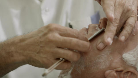 Elderly Barber with Razor Cutting Beard To Client Stock Video Footage