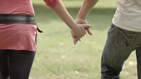 Young Couple Walking Hand in Hand in Park Stock Video Footage