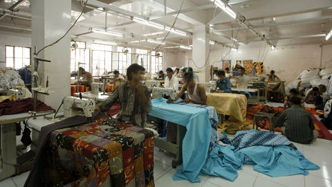 Factory workers using sewing machines in a garment Footage