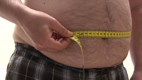 Measuring His Thick Belly stock footage