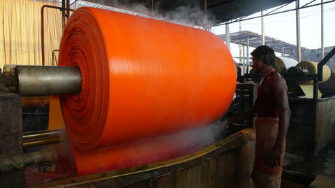 Newly Dyed Fabric Being Washed And Rolled, Sari Ga stock footage
