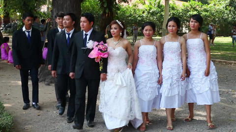 Bride, groom and friends walking in the park Footage