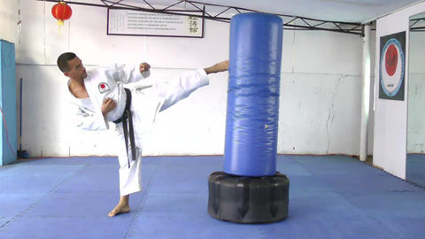 Black belt Karate Man practicing in the sandbag Footage