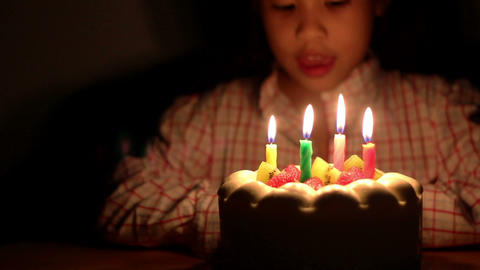 Asian Girl Blowing Birthday Cake Candles