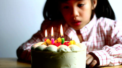 Asian Girl Blowing Birthday Cake Candles 0