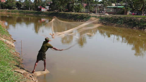 Fisherman casts his net into the river Footage