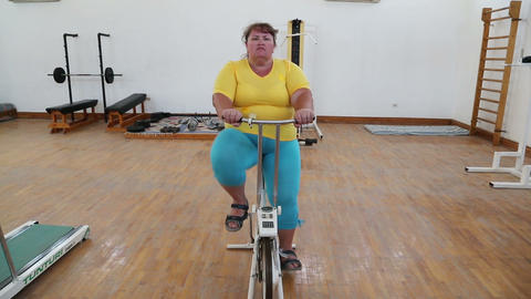Overweight Woman Exercising On Bike Simulator stock footage