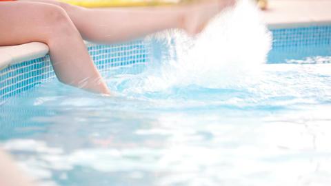 Woman splashing feet in the pool Footage