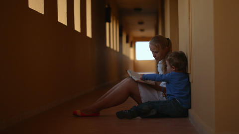 Mother and son with book in hotel hall Footage