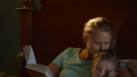 Mother and son in bed with book Footage