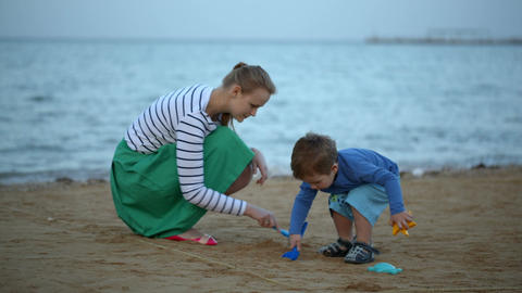 Mother and son playing on the beach Footage
