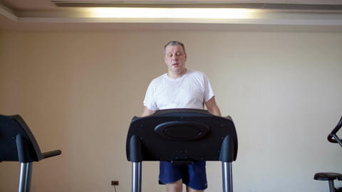 Middle-aged man working out on a treadmill Footage
