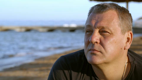 Handsome middle-aged man thinking at the beach Footage