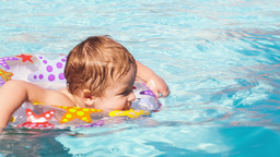 Kid Learns To Swim Using A Plastic Water Ring stock footage