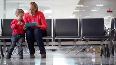 Young mother and son in an airport terminal Footage