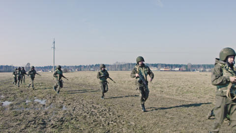 Soldiers with weapons run on camera Footage