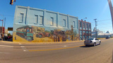 Cars Driving By Historical Mural In Downtown Shawn stock footage