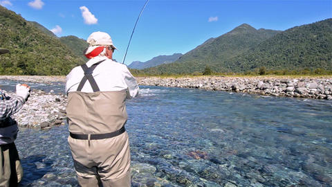 Guest and guide catching a trout while fly fishing Footage