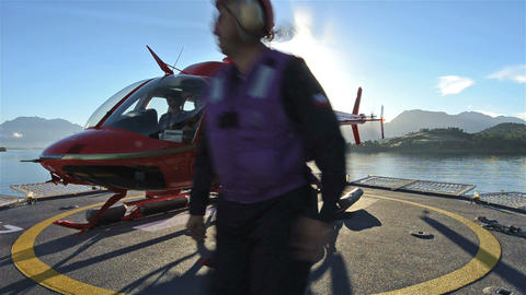 Low angle of crew loading passengers into a helico Footage