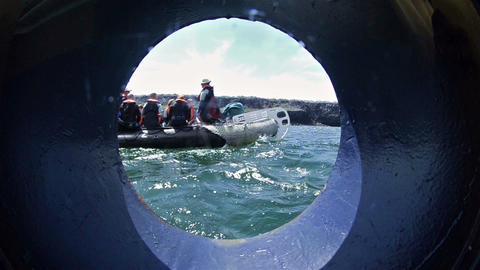 View through a ship's porthole of snorkelers depar Footage