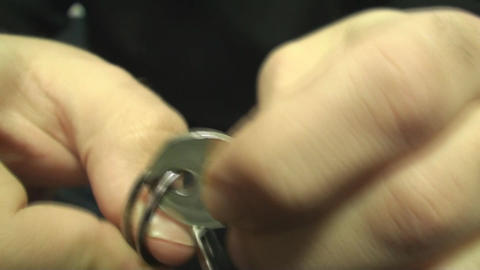 Young Male Adds A Key To The Keychain Front Shot Live Action