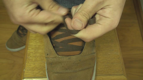 Young Man Ties A Shoelace Above Shot stock footage