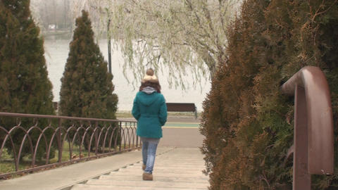 Young Woman Slowly Walks Up The Stairs In The Park Footage