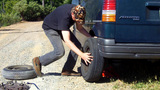 Man Changing Tire On Dirt Road Part 3 stock footage