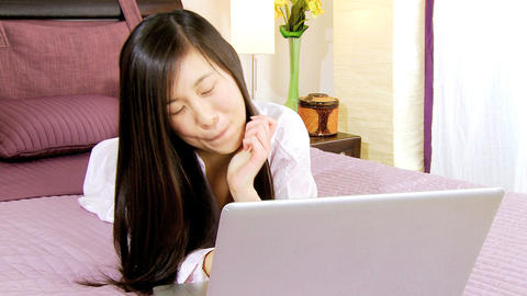 Happy asian woman having fun with pc in bed Footage