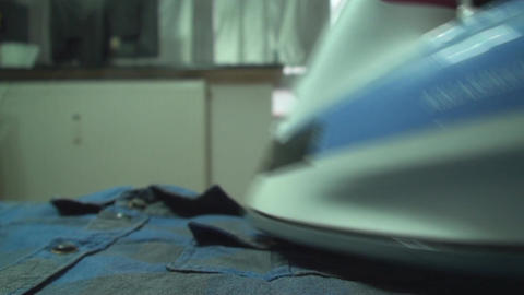 Young Man Ironing A Shirt Front-Shot Footage
